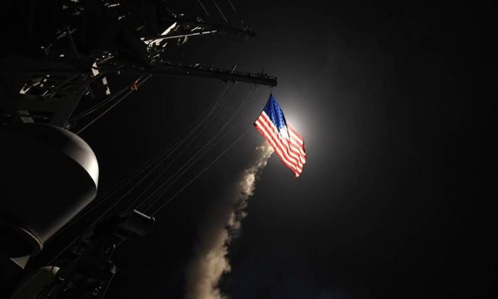 Míssil disparado pelos EUA passa por trás de bandeira americana em navio no Mediterrâneo Foto: AFP