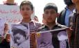 Meninos sírios que moram em Khan Sheikhun, cidade atingida por ataque químico na terça-feira, seguram fotos de vítimas em protesto