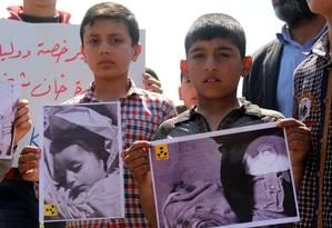 Meninos sírios que moram em Khan Sheikhun, cidade atingida por ataque químico na terça-feira, seguram fotos de vítimas em protesto Foto: OMAR HAJ KADOUR / AFP