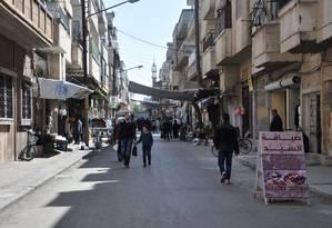 Pedestres caminham pelas ruas de Homs, cidade próxima à base militar síria bombardeada pelos EUA Foto: SANA / REUTERS