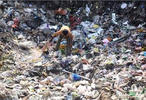 Homem explora lixão em Mumbai, na Índia: legislação ambiental do país não é aplicada Foto: Indranil MUKHERJEE/AFP