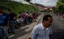 Extensa fila se forma diante de um supermercado do governo: um número no documento indica em qual dia da semana a pessoa pode comprar comida. Os alimentos são poucos Foto: Alejandro Cegarra / Washington Post