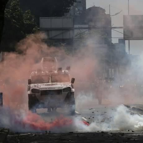 Fumaça vermelha surge perto de veículos das forças de segurança da Venezuela durante protesto em Caracas Foto: Fernando Llano / AP