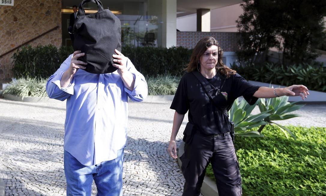 Gustavo Estellita, sócio de Miguel Iskin, presidente da Oscar Iskin, tentou se esconder dos fotógrafos ao ser levado preso pela PF. Foto: Pablo Jacob / O Globo