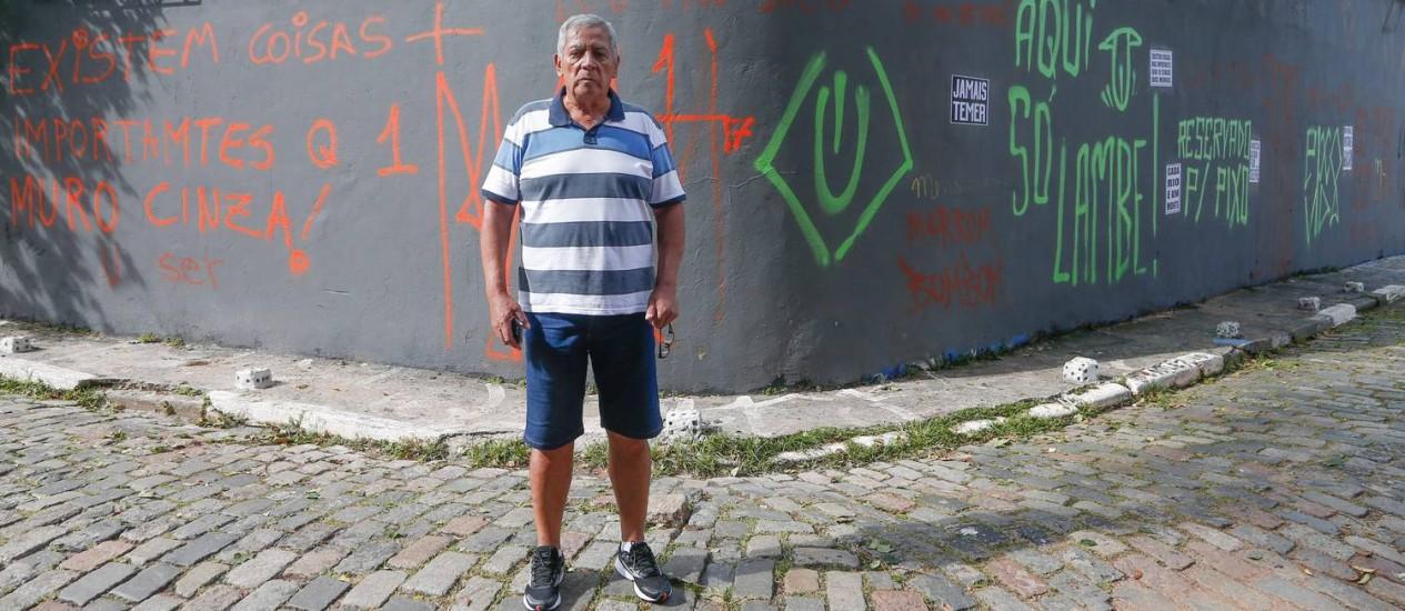 João Batista Silva, morador do Beco do Batman, na Vila Madalena, em SP, dante do muro de sua casa Foto: Marcos Alves / Agência O Globo