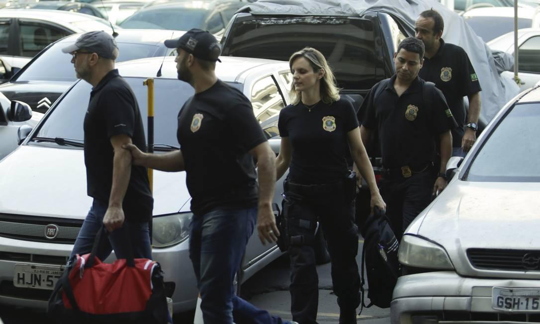 À frente dos policiais — e usando os mesmos trajes —, Côrtes é segurado pelo braço por um PF, enquanto carrega uma bolsa vermelha Foto: Gabriel de Paiva / O Globo
