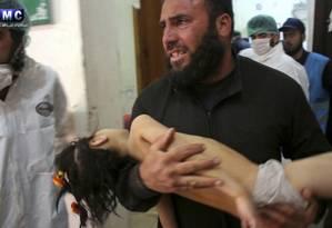 Homem segura criança no colo após ataque químico contra provínca síria de Idlib Foto: Uncredited / AP