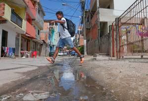 Menino salta por cima de esgoto correndo a céu aberto em comunidade em São Paulo Foto: Marcos Alves / Marcos Alves