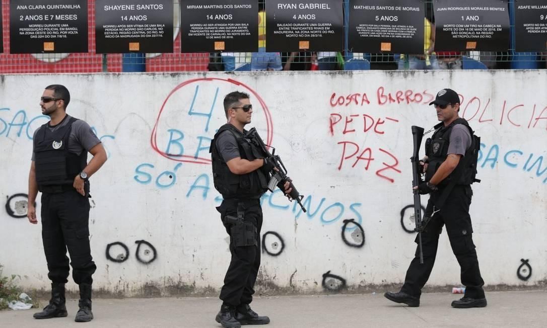 Marcas do confronto. Policiais junto ao muro da unidade de ensino Foto: Marcio Alves / Márcio Alves
