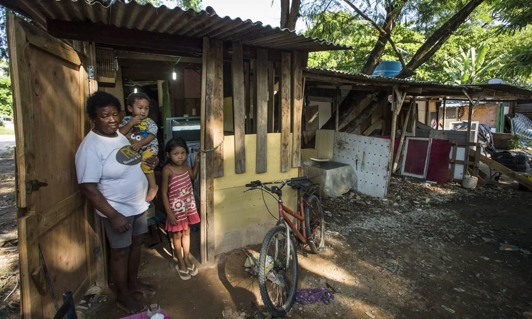 Maria do Carmo Garcia e os netos vivem há 10 anos numa área ocupada por barracos de madeira depois de perderem a casa num incêndio Foto: Guito Moreto / Agência O Globo
