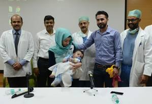 Pais e médicos posam para fotos com Karam após operação de sucesso para remover membros do bebê Foto: MONEY SHARMA / AFP