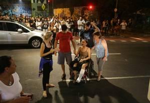 Tayssa Freitas, namorada de Miguel (na cadeira de rodas), chora durante a homenagem que amigos prestaram ao jovem morto no local do crime, em Laranjeiras Foto: Marcelo Theobald / Marcelo Theobald