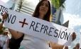 """Uma manifestante segura um cartaz escrito """"não mais repressão"""""""