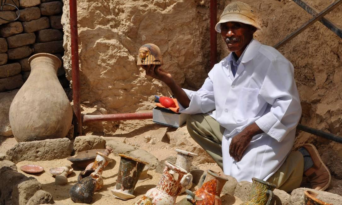 Um membro da equipe arqueológica mostra artefatos descobertos no interior da tumba STRINGER / AFP