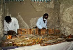 Arqueólogos trabalham na limpeza de sarcófagos encontrados em tumba no Egito Foto: STRINGER / AFP