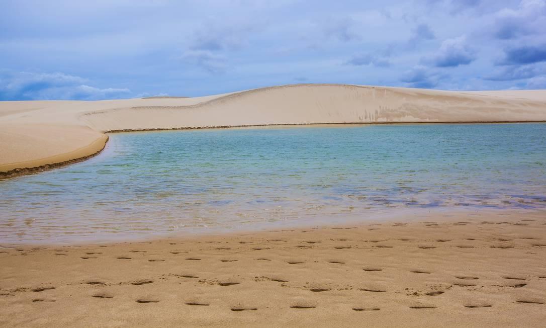 Pegadas na areia ao lado de lagoa no Parque Nacional dos Lençóis Maranhenses. Fora da alta temporada (que começa em junho) os mergulhos ficam menos concorridos, e o paraíso parece quase particular. Foto: Elisa Martins / Elisa Martins