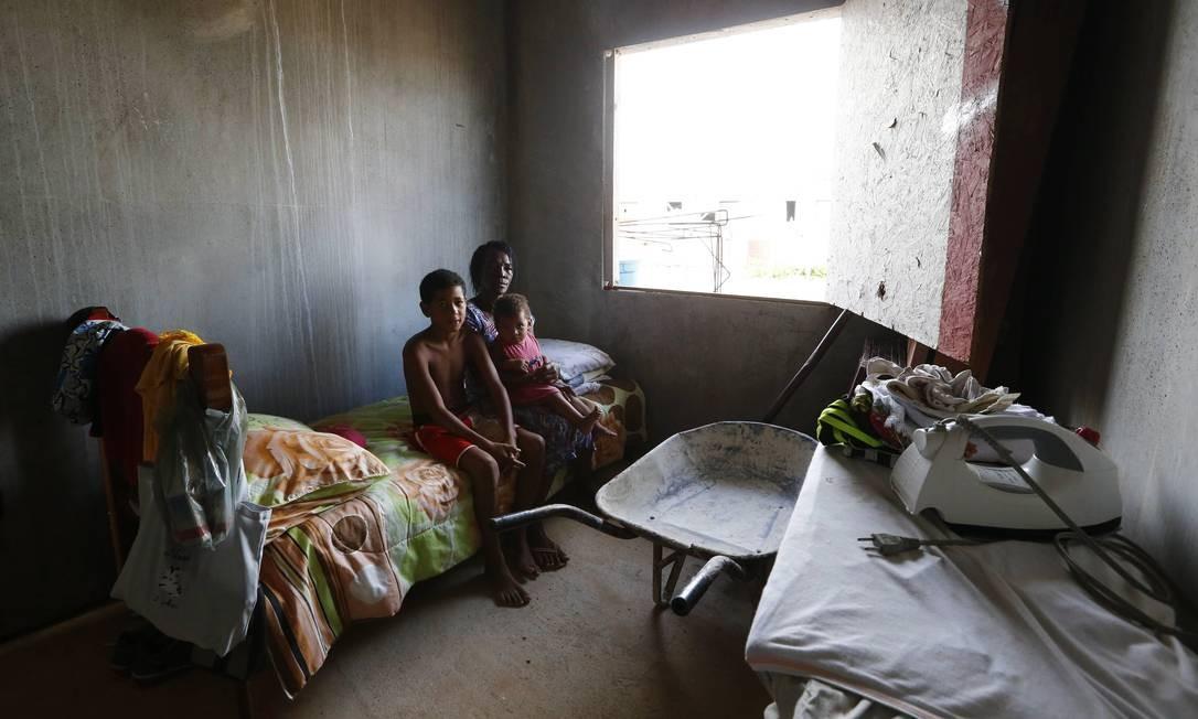 Vilma da Conceição vive com o filho e os netos em uma das casas: sem caixa d'água, usam uma mangueira para tomar banho Foto: Pablo Jacob / Agência O Globo