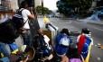 Manifestantes anti-Maduro montam barreira em confronto com policiais