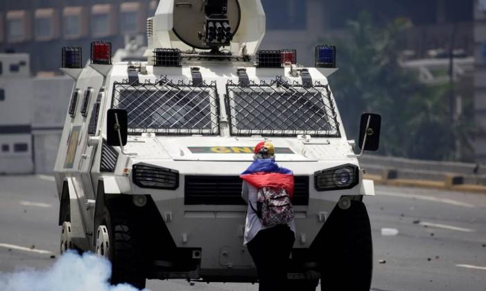 Manifestante impede a passagem de um veículo armado durante o protesto anti-governo, em Caracas, Venezuela Foto: MARCO BELLO/REUTERS