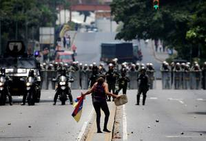 Manifestante fica diante de policias em Caracas Foto: CARLOS GARCIA RAWLINS / REUTERS