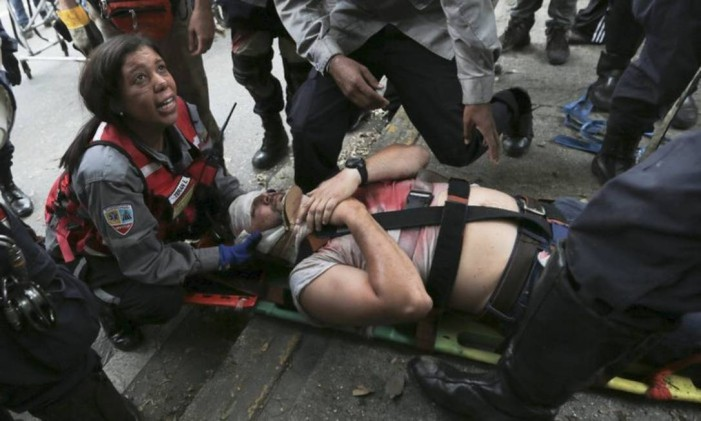 Homem é resgatado após ser ferido e inalar gás em protesto Foto: AP / Fernando Llano