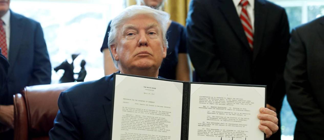 O presidente dos EUA, Donald Trump, exibe ordem assinada por ele para investigação das importações de aço pelo seu país: cargo lhe garante lugar na lista da 'Time' deste ano Foto: AARON P. BERNSTEIN / REUTERS/AARON P. BERNSTEIN