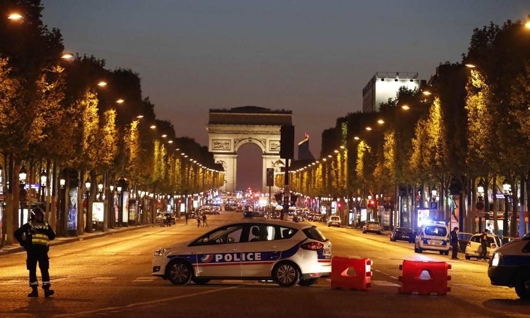 Polícia patrulha a Avenida Champs-Élysées, em Paris, depois de um policial ser morto e outro ferido por um homem armado com uma Kalashnikov CHRISTIAN HARTMANN / REUTERS