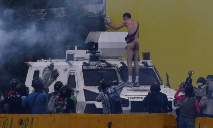 Manifestante nu sobe em um tanque na guarda nacional durante protesto desta quinta-feira Foto: CARLOS GARCIA RAWLINS / REUTERS