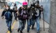 Um jornalista ferido é ajudado por colegas durante protestos em Caracas