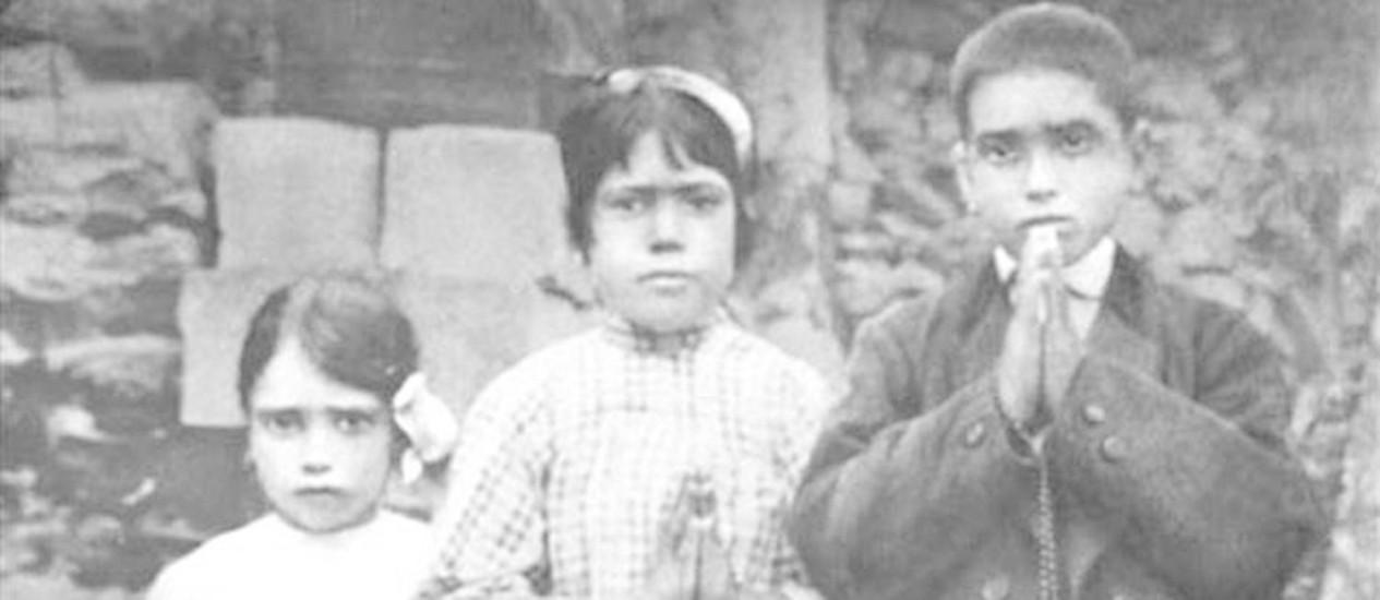 Foto das três crianças pastoras de Fátima, Lúcia (no meio, aos dez anos de idade) e seus dois primos Francisco (nove anos) e Jacinta Marto (sete anos), segurando seus rosários, tirada na época das aparições da Virgem Maria que afirmaram ter presenciado Foto: Reprodução