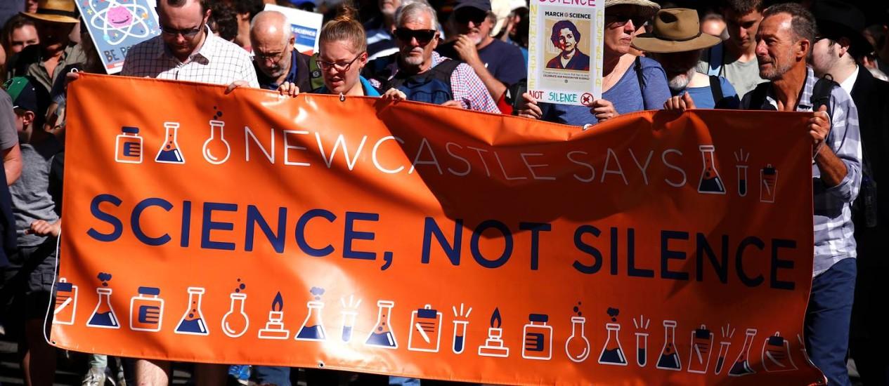 """A marcha foi organizada para acontecer no Dia da Terra, comemorado neste sábado. Na imagem, lê-se na faixa """"Ciência, não silêncio"""" Foto: DAVID GRAY / REUTERS"""
