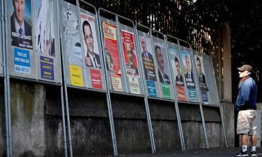 Homem olha para os cartazes dos candidatos a presidente em Enghien-les-Bains, França. Embora 11 concorram ao cargo, quatro estão embolados na disputa, que vai da extrema-esquerda à extrema-direita Foto: CHRISTIAN HARTMANN / REUTERS