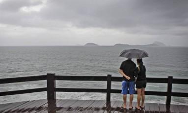 Casal, de guarda chuva, observa mar no Mirante do Leblon Foto: Agência O Globo / Luiz Ackermann