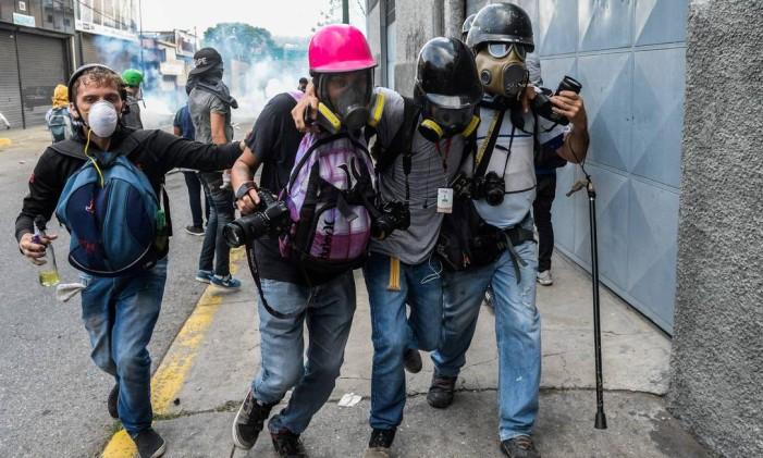 Um jornalista ferido é ajudado por seus colegas durante confrontos com a polícia, em Caracas Foto: FEDERICO PARRA / AFP