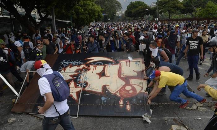 Oposicionistas fazem uma barricada em uma avenida em Caracas Foto: FEDERICO PARRA / AFP