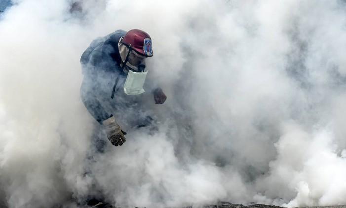 Um manifestante cercado por gás lacrimogêneo durante confronto com a polícia em um protesto contra o presidente da Venezuela, Nicolás Maduro Foto: JUAN BARRETO / AFP