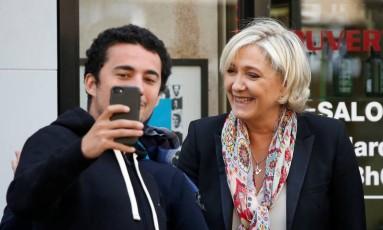 Marine Le Pen faz selfie com eleitor em Paris Foto: CHARLES PLATIAU / REUTERS
