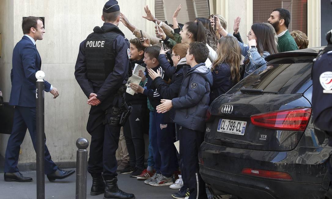O centrista Emmanuel Macron, candidato à Presidência francesa, é cumprimentado por estudantes ao deixar seu apartamento em Paris, nesta segunda-feira. É a primeira vez que nem o partido Os Republicanos nem o Partido Socialista vão para o segundo turno Foto: Thibault Camus / AP