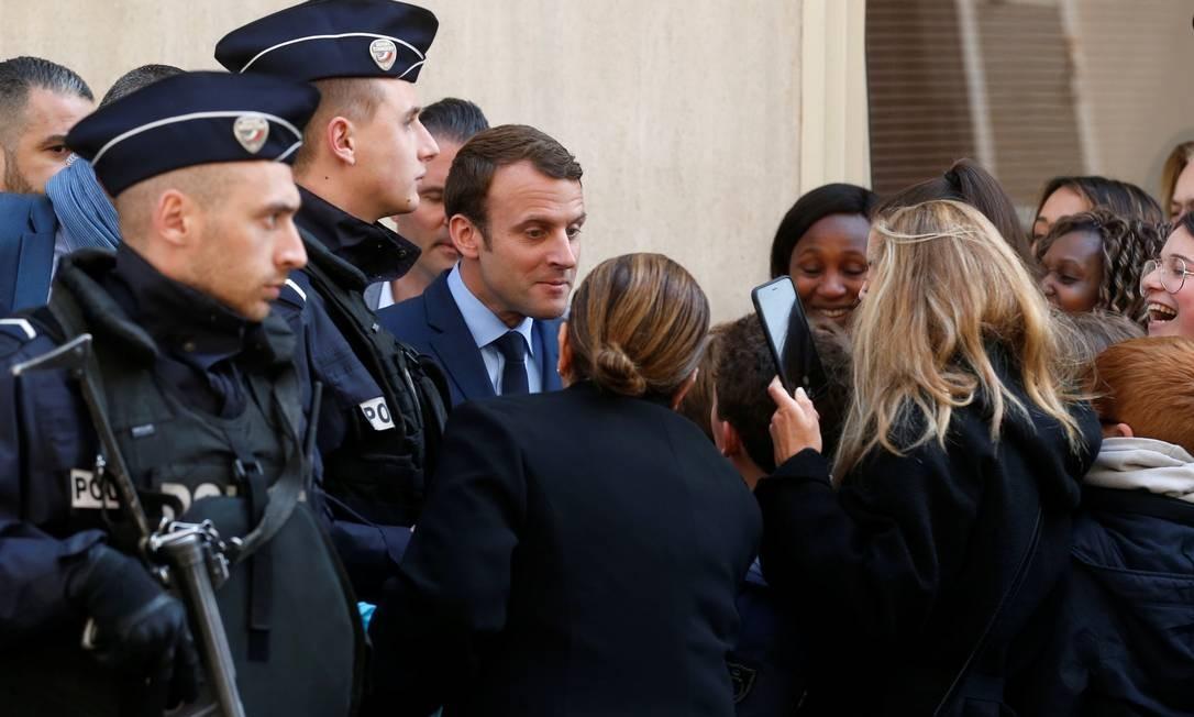 Emmanuel Macron, do movimento político Em Marcha!, fala com eleitores cercado por policiais, ao deixar sua casa em Paris. O candidato se distanciou do presidente socialista François Hollande em agosto de 2016, após dois anos como seu ministro da Economia Foto: BENOIT TESSIER / REUTERS
