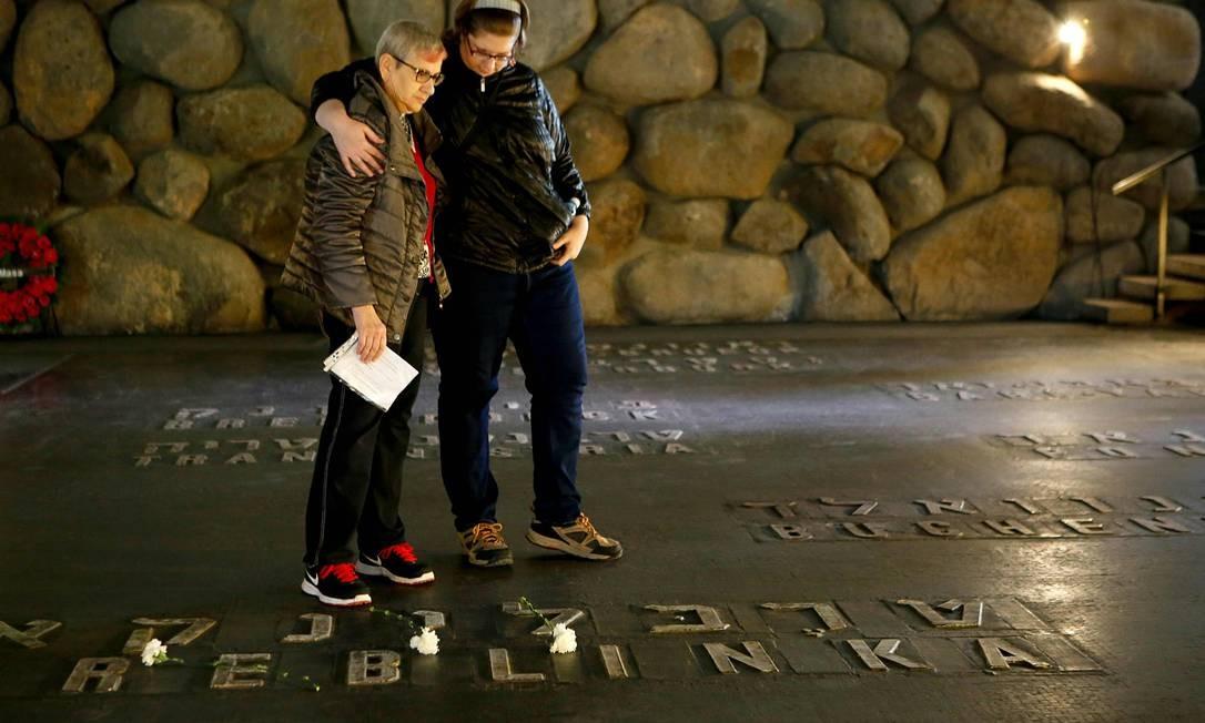 Parentes israelenses de um sobrevivente do Holocausto visitam, nesta segunda-feira, o Salão da Memória, onde os nomes das vítimas dos campos de concentração estão escritos. Israelenses fizeram dois minutos de silêncio enquanto sirenes soavam para lembrar as seis milhões de judeus vítimas do Holocausto Foto: GIL COHEN-MAGEN / AFP