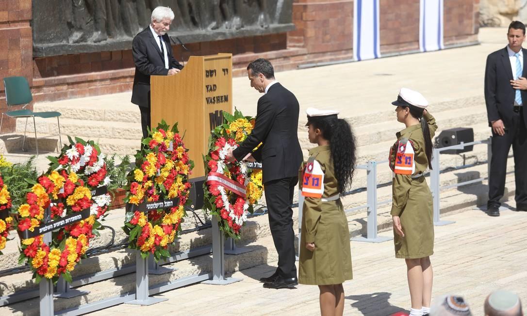 O chanceler da Áustria, Christian Kern, leva uma coroa de flores para a cerimônia do Dia Internacional da Lembrança do Holocausto, em Yad Vashem, Jerusalém, nesta segunda-feira Foto: Dan Balilty / AP