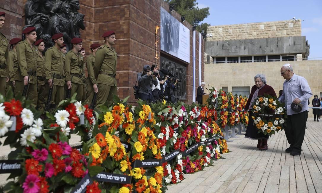 Pessoas deixam coroas de flores para as vítimas do regime nazista em Jerusalém, nesta segunda-feira. Israel lembra hoje os seis milhões de vítimas do Holocausto Foto: Dan Balilty / AP