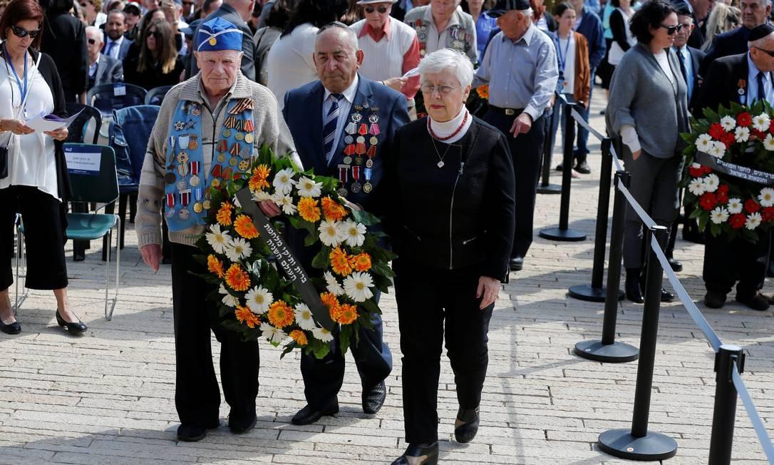 Veteranos da Segunda Guerra Mundial levam uma coroa de flores em homenagem às vítimas da Segunda Guerra Mundial, na cerimônia do Dia Internacional da Lembrança do Holocausto, em Jerusalém Foto: AMIR COHEN / REUTERS