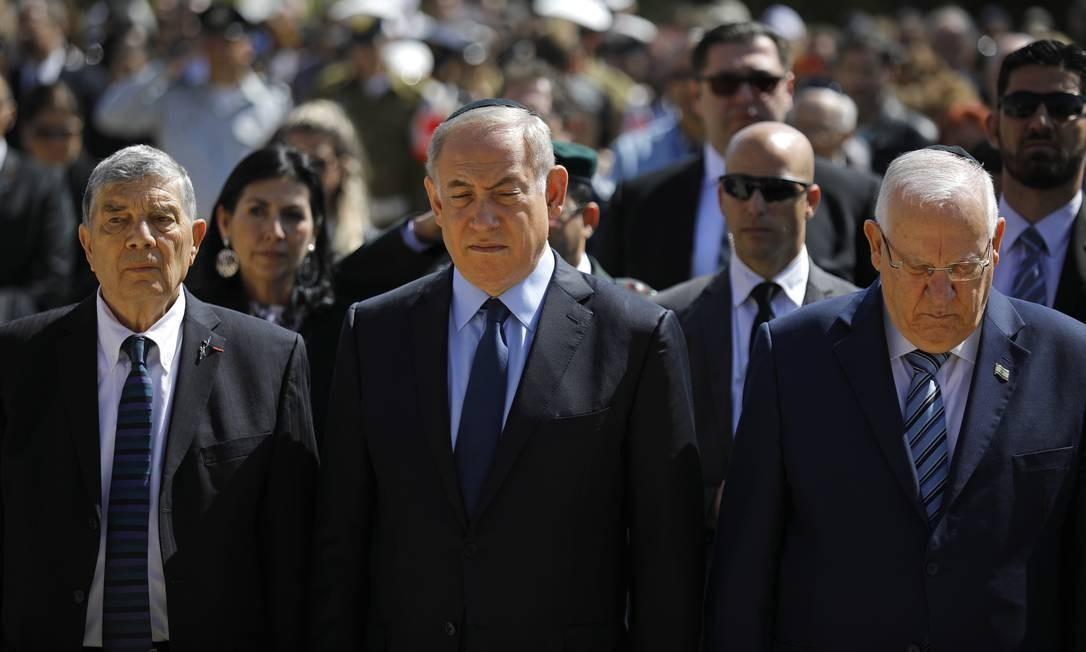 O primeiro-ministro israelense, Benjamin Netanyahu (centro), o presidente israelense, Reuven Rivlin (à dir.), e o presidente do Memorial do Holocausto, Avner Shalev, fazem silêncio enquanto sirenes tocam durante cerimônia que marca o Dia Internacional da Lembrança do Holocausto Foto: AMIR COHEN / AP