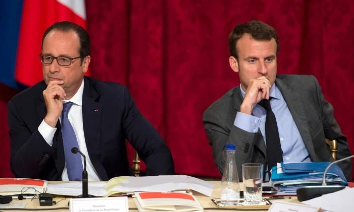 Em junho de 2015, presidente francês, François Hollande, e então ministro da Economia, Emmanuel Macron, se sentam lado a lado em reunião de conselho estratégico Foto: LIONEL BONAVENTURE / AFP