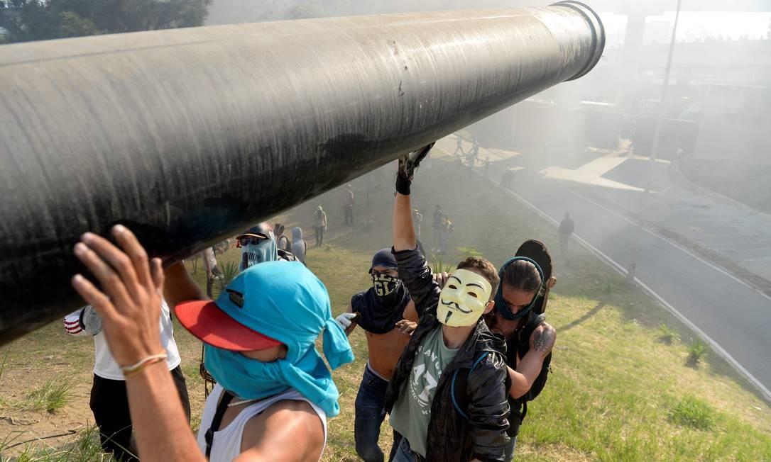 Opositores do governo carregam cano para montar barricada Foto: FEDERICO PARRA / AFP