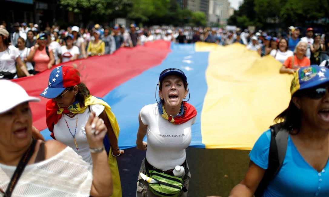 A bandeira nacional foi levada por mulheres que gritavam slogans contra o governo Foto: CARLOS GARCIA RAWLINS / REUTERS