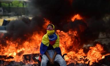 Manifestante da oposição a Maduro vigia barricada com fogo em avenida de Caracas Foto: RONALDO SCHEMIDT / AFP