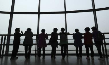 Visitantes observam a Coreia do Norte nesta terça-feira, no observatório da unificação em Paju, na Coreia do Sul. O governo de Seul anunciou exercícios com um porta-aviões americano, que já chegou à península coreana Foto: Lee Jin-man / AP