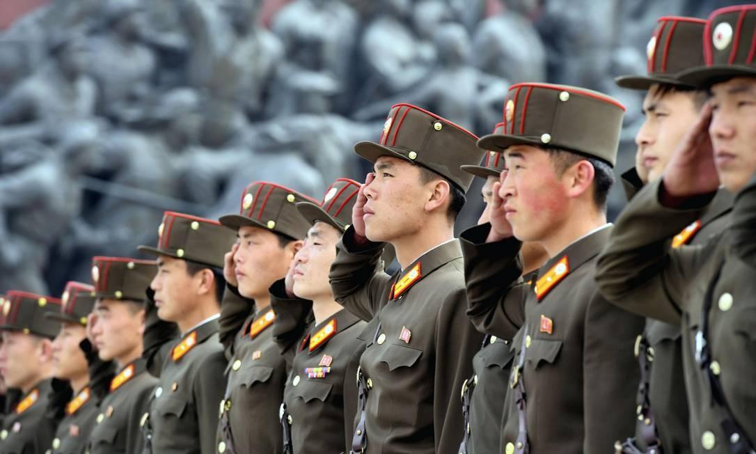 Soldados norte-coreanos saúdam estátuas de bronze do fundador do regime do país, Kim II-Sung, e do ex-líder Kim Jong-II, respectivamente avô e pai de Kim Jong-Un. O país realizou o maior exercício de tiros nesta terça-feira, comemando o aniversário de 85 anos das suas forças armadas Foto: KYODO / REUTERS
